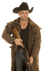 cowboy in black hat and duster hold rifle look