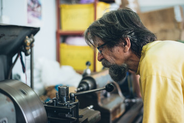 Portrait of a serious bearded worker with glasses doing some job on metalworking machine. Selective focus.