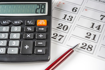 Calculator And Pen Resting On An Calendar
