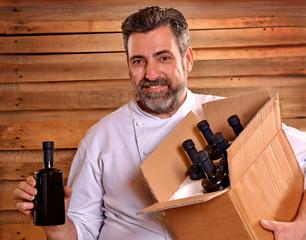 Cocinero sujetando una caja con botellas de aceite de oliva,aceituna.