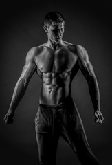 Sexy muscular man posing with naked torso on black background
