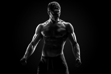 Sexy muscular man posing with naked torso on black background Wall mural