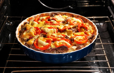Potato with meat, tomato and cheese is baked in the oven.