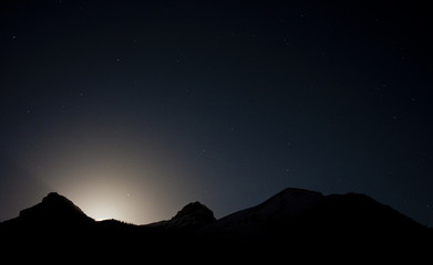 moon set behind the mountain silhouettes