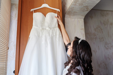 Beautiful bride in the morning of wedding day with her dress trying