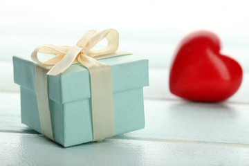Gift box and decorative hearts on color wooden table, on light background