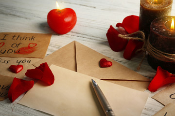 Gift card for Valentine's Day with inscriptions, pen and candles on white wooden background