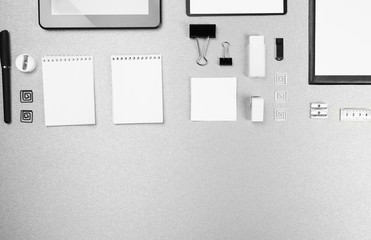 Office set with white sheets of paper, tablet and stationery on grey background