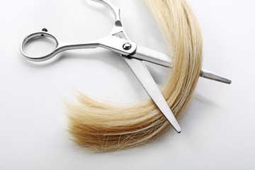Hairdresser's scissors with strand of blonde hair, isolated on white