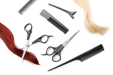Hairdresser's scissors with combs, clip and strands of hair, isolated on white