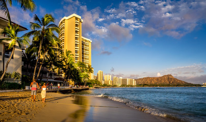 Waves crashing on famous Waikiki beach in Honolulu Hawaii at sunset.