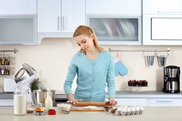 Young woman rolling out the dough on the kitchen counter