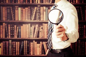 虫眼鏡をカメラに向けているビジネスマン,本棚の背景,コピースペース