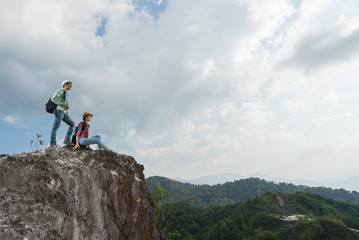 Travel concept. Young tourists with backpacks enjoying valley view from top of a mountain