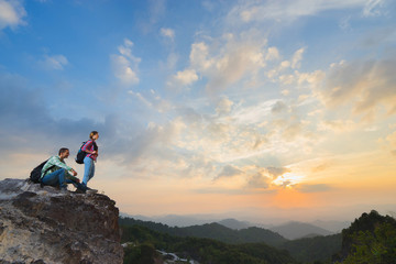 Young backpackers enjoying a valley view from top of a mountain in sunset. Travel concept.