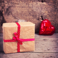 Gift box  and decorative red  heart on  vintage  wooden backgrou