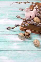 Quail eggs, decorative hen, willow  branches on wooden backgroun