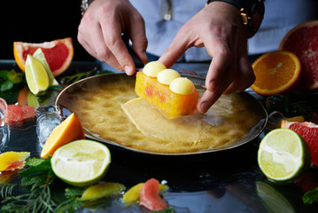 Hand made citrus tart with chef's hand