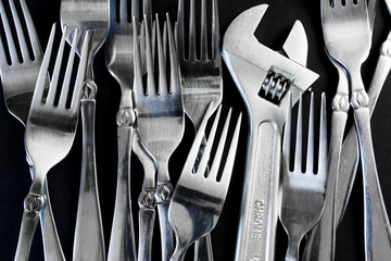 Set of forks, and wrench on a black background
