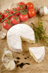 camembert with garlic, black pepper, tomato and thyme on brown p