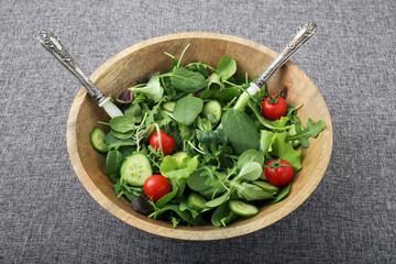 insalata verde pomodori e cetrioli in ciotola di legno sfondo grigio