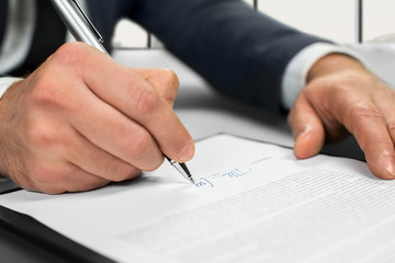 Businessman signing contract at office.
