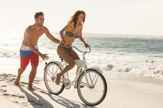 Couple going on a bike ride on the beach