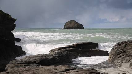 Fototapete - View out to sea to Gull Rock with waves crashing on the rocks Trebarwith Strand Cornwall England UK