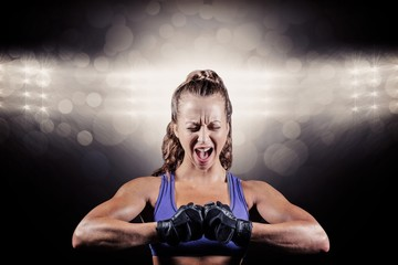 Composite image of aggressive female boxer flexing muscles