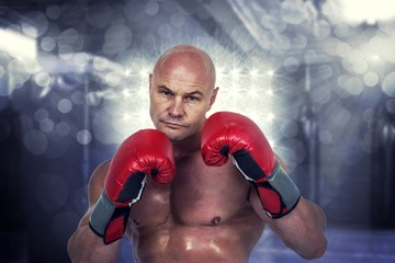 Composite image of portrait of bald boxer in red gloves