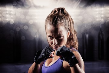 Composite image of portrait of woman with fighting stance