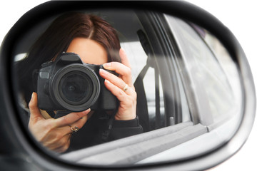 Photographer using his professional camera. Photographer girl  in the car window. Mobile reporter with the DSLR camera. Photojournalist at work. Photographer on walk with a professional camera.