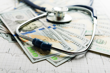 Dollars with stethoscope on them. Costs for the medical insuranc