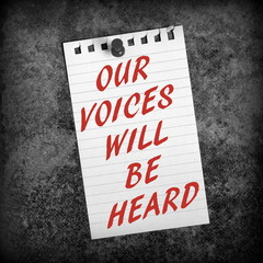 The message Our Voices Will Be Heard in red text on a scrap of lined paper pinned to a grunge background in black and white for effect