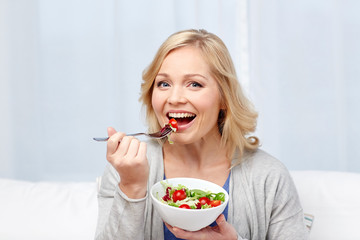 smiling middle aged woman eating salad at home