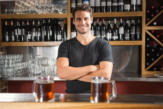 Handsome bar tender standing behind his counter