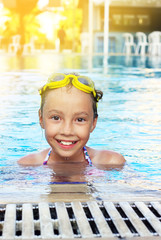 Cute little girl is smiling in swimming pool