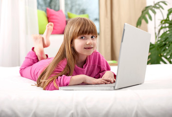 Preschool young girl lying in bed and play on the computer