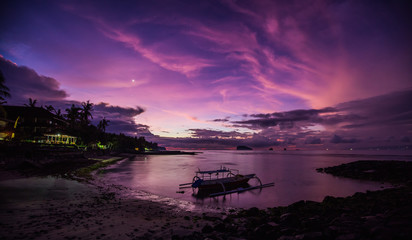 Indonesian tropical sunrise with the Venus visible and fisherman boat