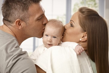 Parents kissing baby's head