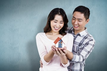 Composite image of happy couple holding a model house
