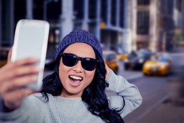 Composite image of asian woman taking selfie