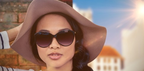 Composite image of asian woman with hat and sunglasse