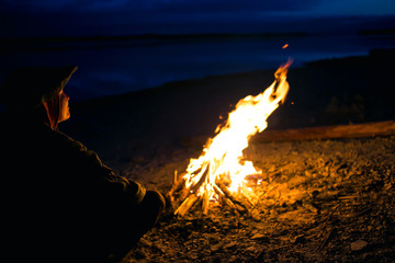 the silhouette of girl tourist around the campfire at night on the river shore