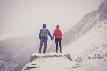 A man and a woman at the top of a snowy mountain