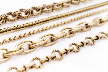 Beautiful Antique Gold Chains in Selective Focus on a White Background