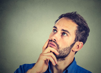 man resting chin on hand thinking daydreaming, staring thoughtfully upwards