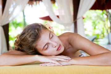 beautiful young woman enjoying her time in tropical spa