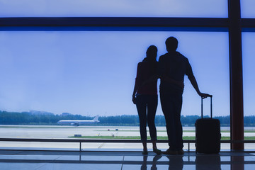 Silhouette of a couple holding hands and waiting at airport terminal