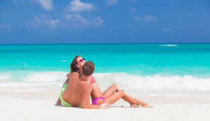 back view of couple sitting on a tropical beach in Barbados